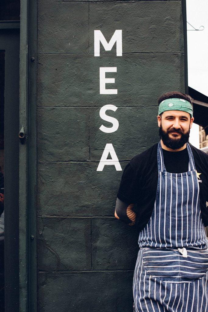 Mesa chef next to logo outside