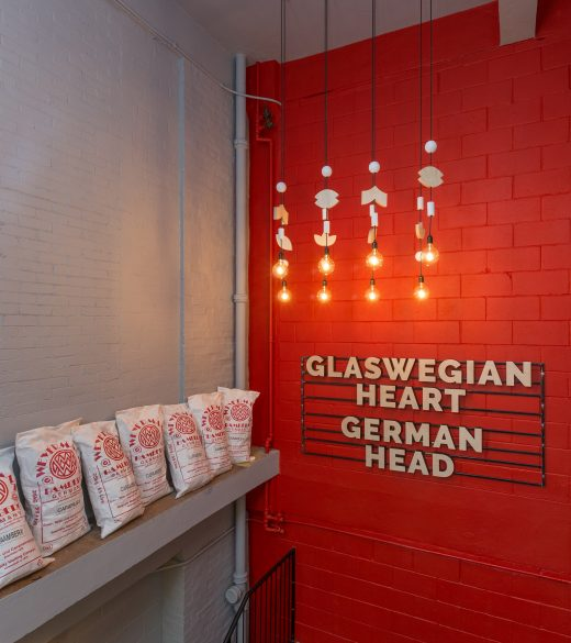 WEST Wooden brand element in Red hallway - 3D wooden signage and wooden icon light fittings
